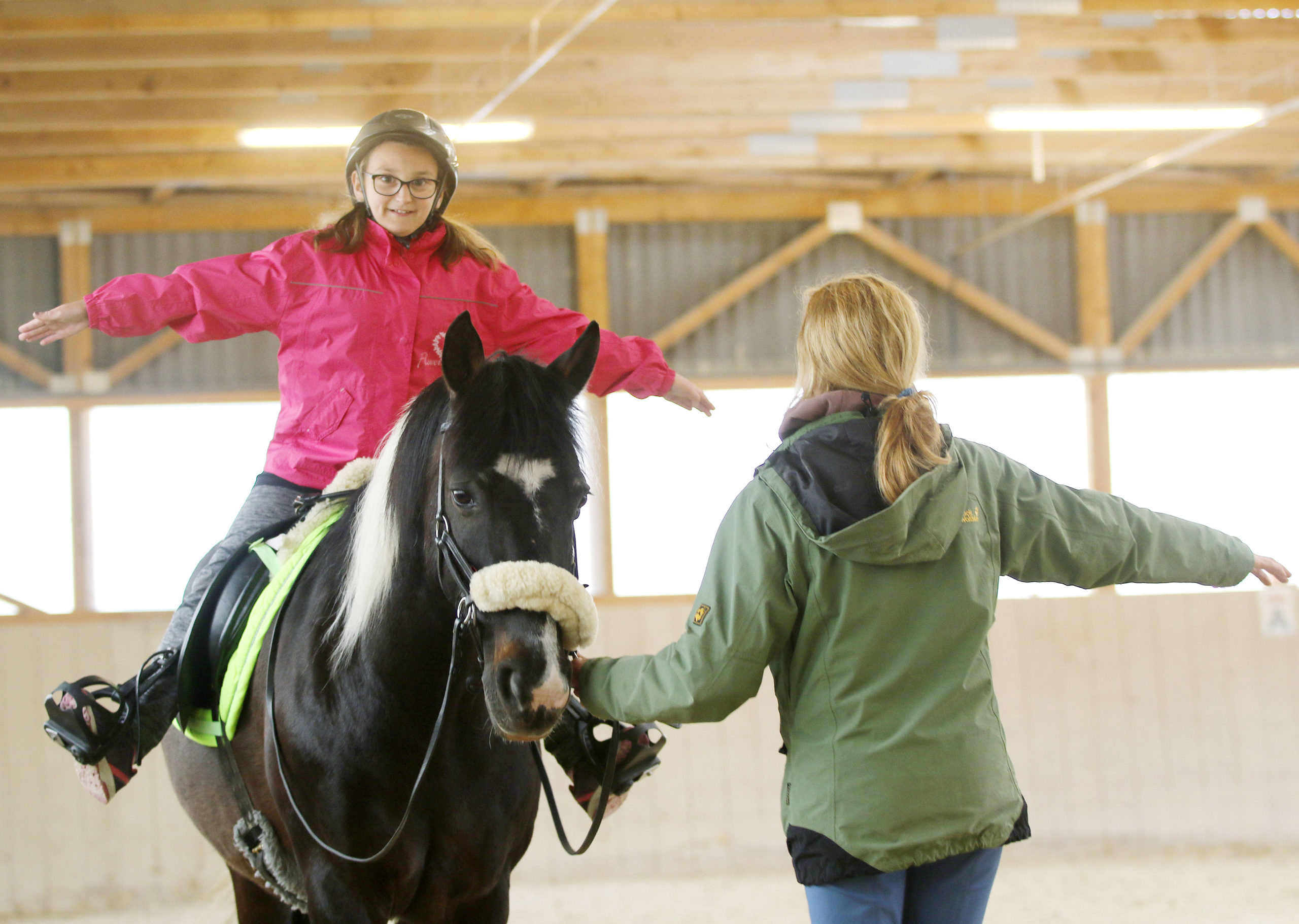 Kind auf Pferd mit Reitlehrerin
